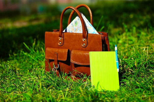 レトロな茶色の男革バッグと公園の明るいカラフルな夏の草のノート