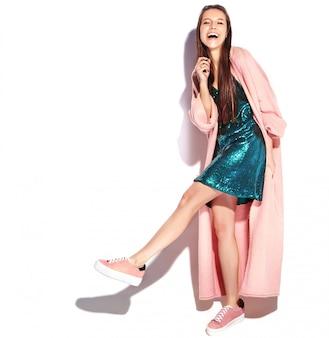 スタイリッシュなピンクのオーバーコートで美しい笑顔ヒップスターブルネットの女性モデル。ウォーキング、フルレングス