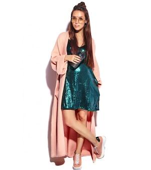 スタイリッシュなピンクのオーバーコートで美しい笑顔ヒップスターブルネットの女性モデル。コーヒーを飲む、全長