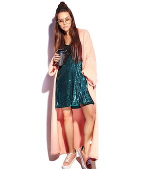 Красивая улыбающаяся хипстерская модель женщины брюнетки в стильном розовом пальто. пить кофе, полная длина