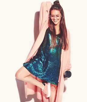 スタイリッシュなピンクのオーバーコートで美しい笑顔ヒップスターブルネットの女性モデル。コーヒーを飲んでいる