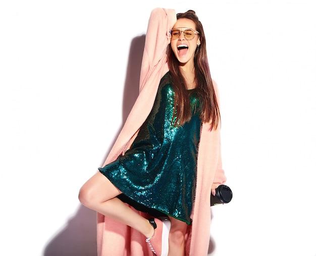Красивая улыбающаяся хипстерская модель женщины брюнетки в стильном розовом пальто. пить кофе