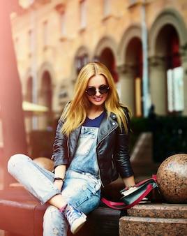 メガネのベンチでジーンズの公園で屋外に座って明るいモダンな布でかわいい面白いモダンなセクシーな都市若いスタイリッシュな笑顔の女性女の子モデルの肖像画