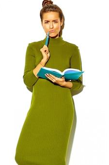 勉強しながら考えてカラフルなノートと青いペンを保持している白で隔離されるカジュアルな緑のヒップスター夏服で美しい幸せなかわいい笑顔ブルネット少女学生の肖像画