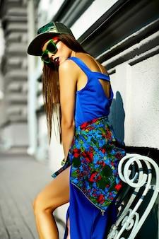 ファッション面白いグラマースタイリッシュなセクシーな笑みを浮かべて美しい若い女性モデルのキャップで通りに青いヒップスター夏服