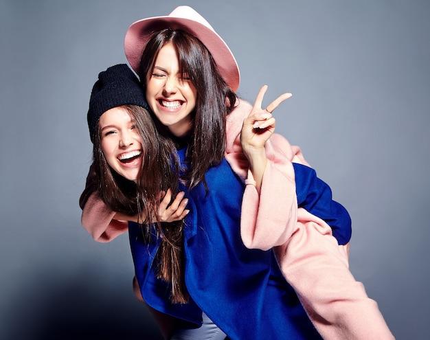 Портрет моды двух улыбающихся моделей брюнетки в летнем повседневном хипстерском пальто, излагающем. девушки держат друг друга на спине