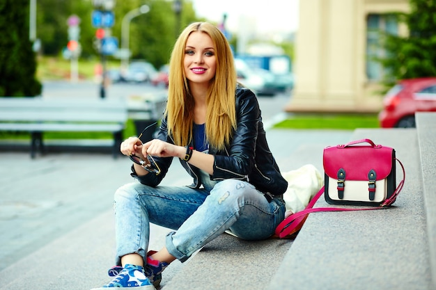 ピンクのバッグとメガネのベンチでジーンズの公園で屋外に座って明るいモダンな布でかわいい面白いモダンなセクシーな都市若いスタイリッシュな笑顔の女性女の子モデルの肖像画
