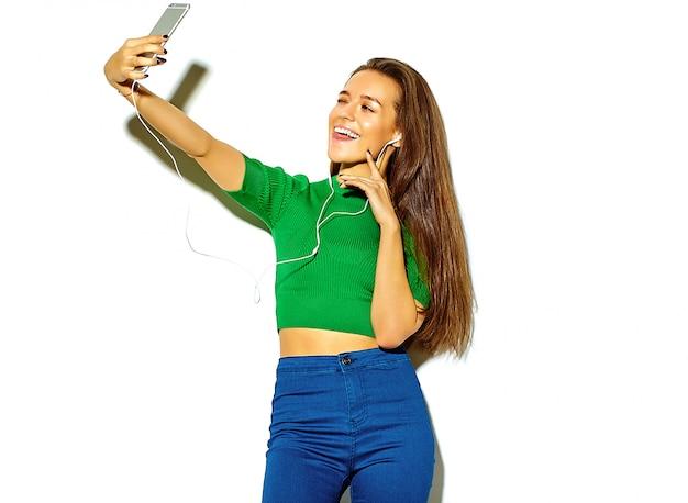 Портрет красивой счастливой милой брюнетки девушки в повседневной зеленой хипстерской летней одежде без макияжа, изолированной на белом, делающей селфи и показывающей ей язык