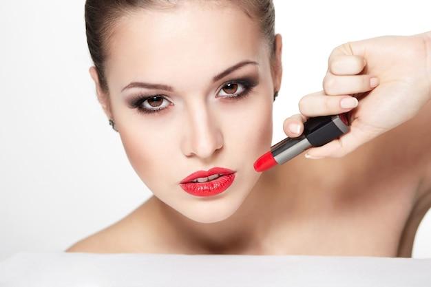 Макрофотография портрет сексуальные кавказские молодой женщины модели с гламур красные губы, яркий макияж, макияж глаз стрелки, цвет чистоты с красной помадой. идеально чистая кожа