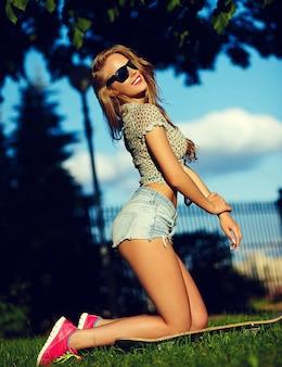 メガネでスケートボードとジーンズのショートパンツで公園で屋外の完璧な日光浴の体と明るいモダンな布でかわいい面白いセクシーな若いスタイリッシュな笑顔の女性女の子モデルの肖像画