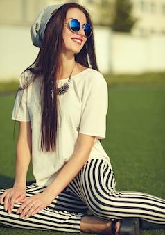 公園の通り背景にポーズをとって夏流行に敏感なカジュアルな服でファッションスタイリッシュな美しい若いブルネットの女性モデル