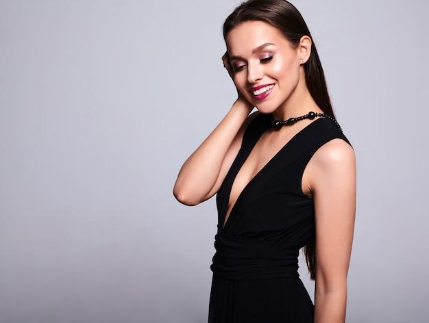 夜のメイクと灰色の分離した赤い唇と黒のドレスで美しい笑顔ブルネットの女性モデルの肖像画