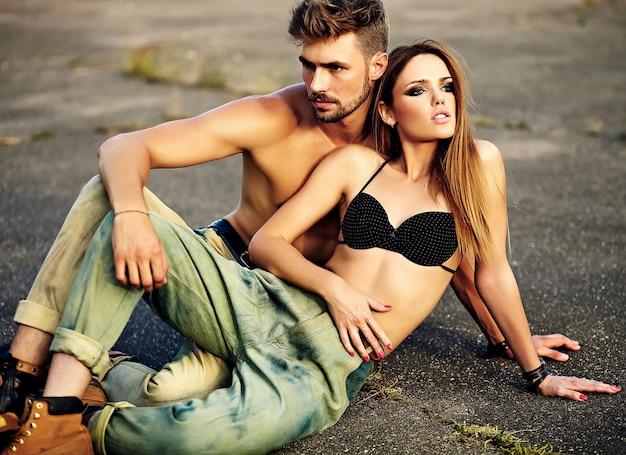 美しいカップルの肖像画。完璧な日光浴肌とアスファルトの背景に屋外のジーンズでハンサムな筋肉男と明るいメイクでセクシーなスタイリッシュな金髪の若い女性モデル