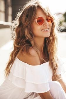 通りの背景の上に座って夏流行に敏感な白いドレス服で化粧なしで美しいかわいい金髪ティーンエイジャーモデルの肖像