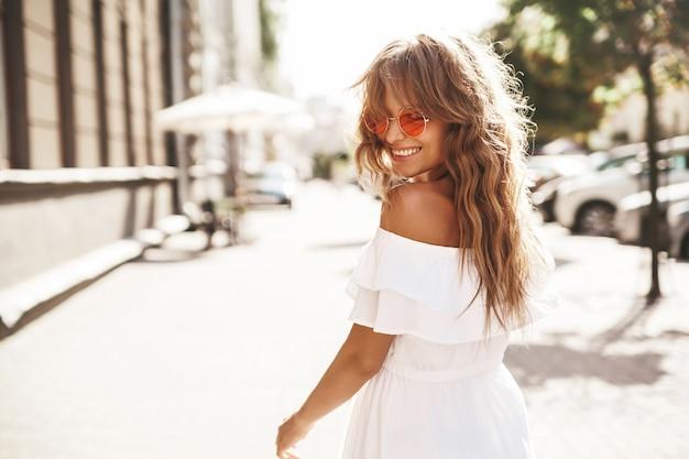 サングラスの路上で実行されている夏流行に敏感な白いドレスで化粧をしない美しいかわいい笑顔金髪ティーンエイジャーモデル。振り向く