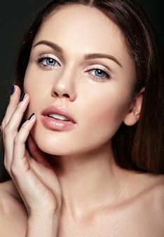 暗い背景にポーズをとって彼女の完璧なきれいな肌に触れる裸化粧と美しい官能的な白人の若い女性モデルの魅力クローズアップ美容肖像画
