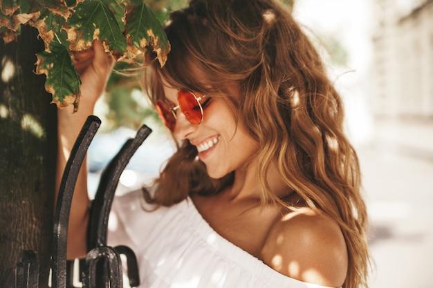 サングラスの通り背景にポーズをとって夏流行に敏感な白いドレス服でメイクなしで美しいかわいい金髪ティーンエイジャーモデルの肖像