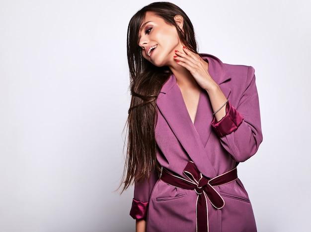 グレーに分離された化粧なしでピンクの衣装で美しいブルネットの女性モデルの肖像画