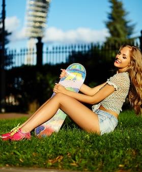 スケートボードとジーンズのショートパンツで公園で屋外の完璧な日光浴ボディと明るいモダンな布でかわいい面白いセクシーな若いスタイリッシュな笑顔の女性女の子モデルの肖像画