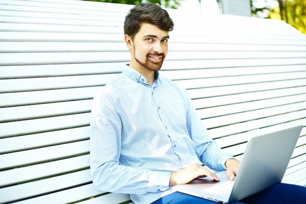 カジュアルな流行に敏感な布でラップトップを使用して公園のベンチに座っている若いハンサムな笑みを浮かべて実業家モデル
