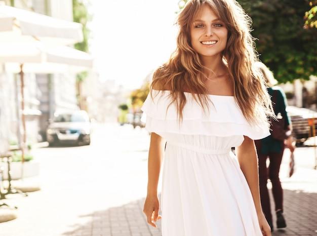 通りの背景にポーズをとって夏流行に敏感な白いドレス服でメイクなしで美しいかわいい金髪ティーンエイジャーモデルの肖像