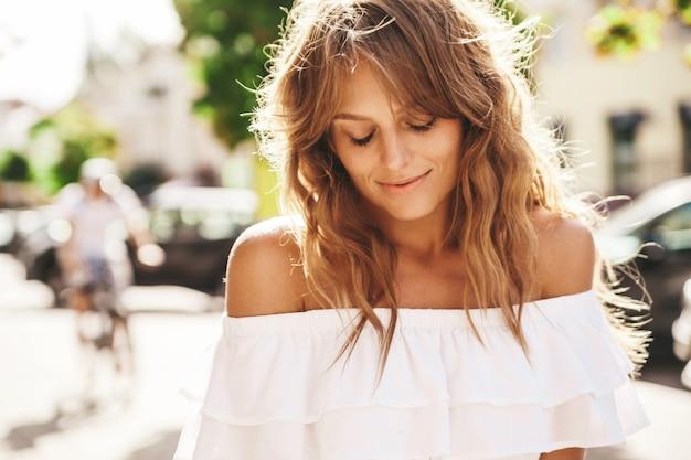 通りの背景にポーズをとって夏流行に敏感な白いドレス服で化粧なしで美しいかわいい金髪ティーンエイジャーモデルの肖像画。目を閉じて