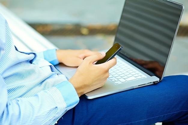 若い男がノートパソコンで作業、ノートパソコンの男の手、通りでカジュアルな服装のビジネス人