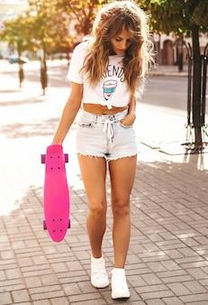 通りの背景にポーズをとってピンクのペニースケートボードと夏流行に敏感な白い服でメイクなしの美しいかわいい金髪ティーンエイジャーモデル