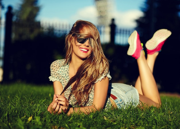メガネのジーンズのショートパンツで緑の芝生の公園で横になっている完璧な日光浴ボディと明るいモダンな布でセクシーなかわいい面白い若いスタイリッシュな笑顔の女性女の子モデルの肖像画