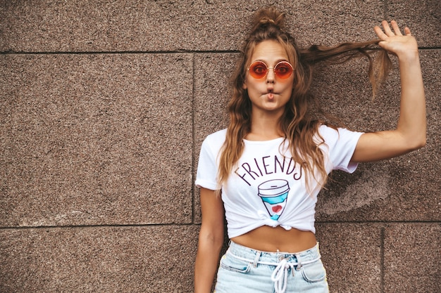 Красивая милая белокурая модель подростка в одеждах битника лета белых представляя около стены на улице. создание смешного рыбьего лица