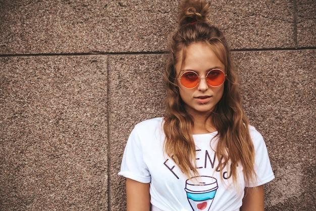 通りの壁に近いポーズ夏流行に敏感な白い服で美しいかわいい金髪ティーンエイジャーモデル