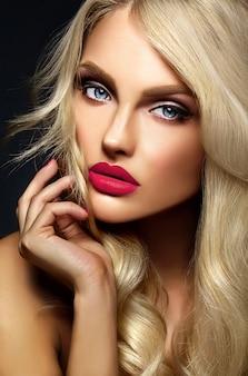 黒の背景に健康的な巻き毛の明るいメイクとピンクの唇、美しい金髪の女性モデルの女性の官能的な魅力の肖像画