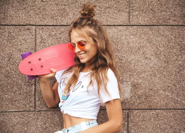 路上の壁に近いポーズピンクペニースケートボードと夏流行に敏感な白い服で化粧なしの美しいかわいい金髪ティーンエイジャーモデル