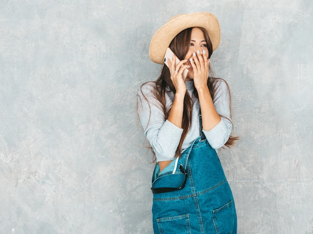 電話で話す若い美しい女性。カジュアルな夏のオーバーオールの服と帽子でトレンディなショックを受けた少女。おかしくて驚いた。彼女の口を閉じる