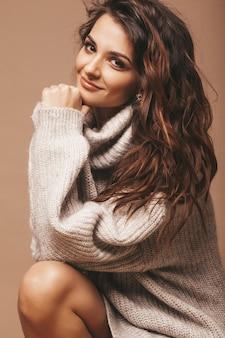 Портрет красивой сладкой милой улыбающейся брюнетки. девушка в повседневной серый свитер. модель позирует в студии. сидя на стуле