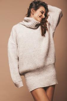 Портрет красивой сладкой милой улыбающейся брюнетки. девушка в повседневной серый свитер. модель позирует в студии