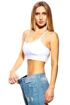 白で隔離され、大きなジーンズと美しい若い女性
