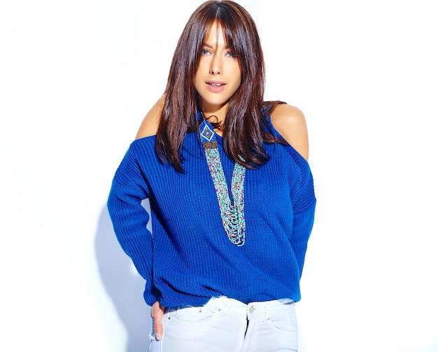 白い背景に分離されたカジュアルなスタイリッシュな夏の青いセーターで流行に敏感なブルネット美人モデル
