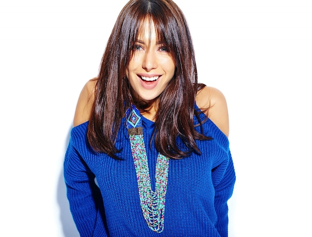 白い背景に分離されたカジュアルなスタイリッシュな夏の青いセーターで美しい笑顔ヒップスターブルネットの女性モデル