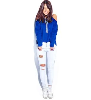 白い背景に分離されたカジュアルなスタイリッシュな夏の青いセーターで美しい笑顔ヒップスターブルネットの女性モデル。