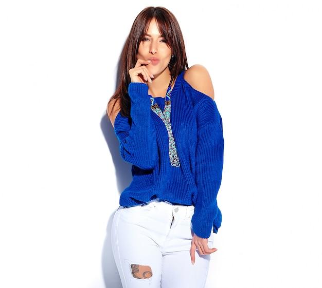 白い背景に分離されたカジュアルなスタイリッシュな夏の青いセーターで美しい面白い流行に敏感なブルネットの女性モデル