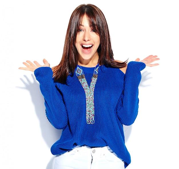白い背景に分離されたカジュアルなスタイリッシュな夏の青いセーターで美しい驚いて流行に敏感なブルネットの女性モデル