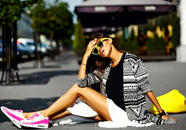 ファッション面白いグラマースタイリッシュなセクシーな笑みを浮かべて美しい若い女性モデルの明るい黄色のバッグをショッピングで通りに座っている流行に敏感な夏服