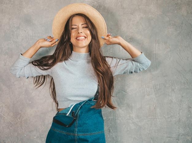 探している若い美しい笑顔の女性の肖像画。カジュアルな夏のオーバーオールの服と帽子でトレンディな女の子。