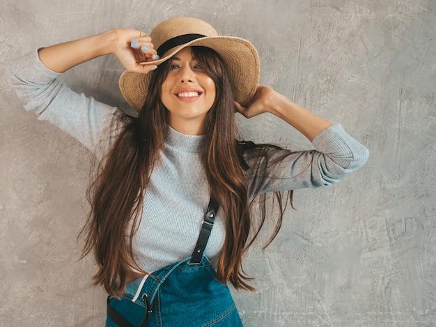 探している若い美しい女性。カジュアルな夏のオーバーオールの服と帽子でトレンディな女の子。