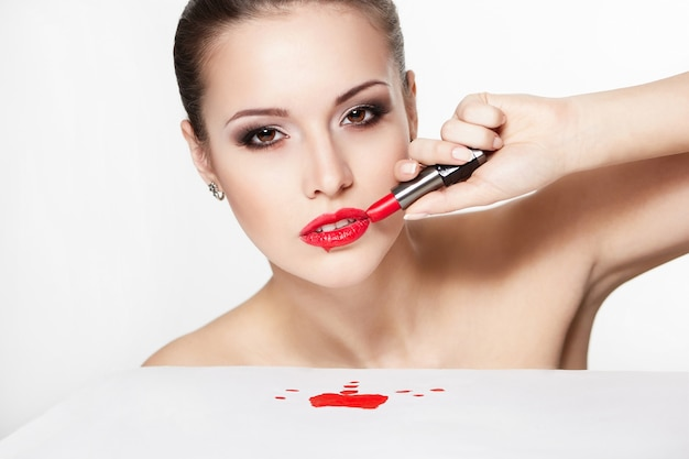 Макрофотография портрет сексуальные кавказские молодой женщины модели с гламур красные губы, яркий макияж, макияж глаз стрелки, цвет чистоты с красной помадой. идеально чистая кожа. кровь на столе
