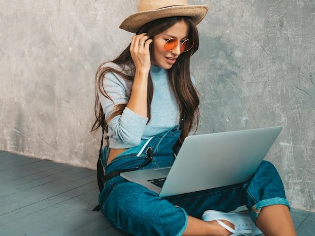 サングラスで創造的な若い笑顔の女性の肖像画。灰色の壁の近くの床に座って美しい少女。