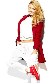 Портрет красивой счастливой сладкой улыбающейся блондинки девушки в повседневной хипстерской теплой зимней одежде, в красной куртке