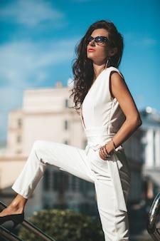 女性モデルの肖像画。白いスーツが路上でポーズの熱い女の子。サングラスのファッション女性