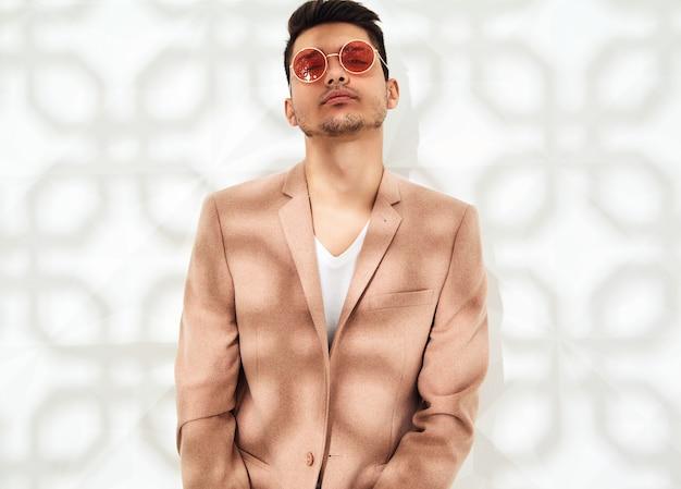 Модная стильная модель в элегантном светло-розовом костюме позирует возле белой стены